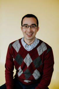 Headshot of smiling man in sweater
